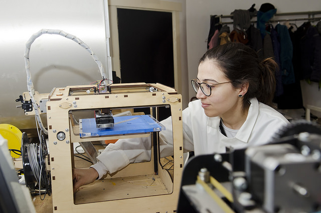 Maker in lab coat using a 3D printer